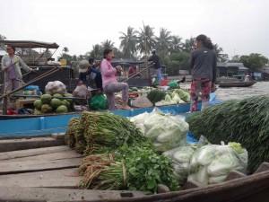 Südvietnam | Can Tho, Frauen beim Verkauf von Gemüse auf dem schwimmenden Markt. Verschiedene Bündel vietnamesischer Gemüsesorten werden auf den Booten zum Verkauf angeboten