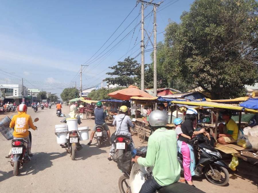 Vietnam | Süden, Phu Quoc, Duong Dong Town. Blick auf die Piste mit zahlreichen Mopeds und Verkaufsständen am Straßenrand