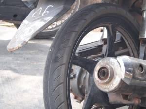 Vietnam | Süden, Phu Quoc. Ein 6 cm langer Nagel steckt in unserem Reifen. Nahaufnahme des Reifens und Auspuff des Mopeds