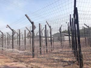 Vietnam | Süden, Phu Quoc Prison. Der Stacheldrahtzaun aus der Nähe mit den Gefängniszellen im Hintergurnd