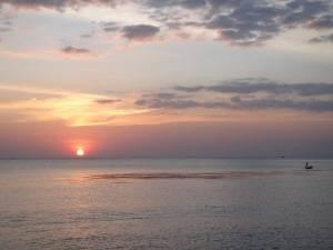 Südvietnam | Phu Quoc, Sonnenuntergang im Mango Bay Resort . Blick auf die rote Sonne am Horizont und ein kleines Fischerboot