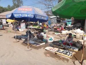 Vietnam | Süden, Verkauf von Fisch nahe Duong Dong auf Phu Quoc. Drei Vietnamesen sitzen hinter ihren zum Verkauf ausgebreiteten Fischen auf dem Boden unter Sonnenschirmen
