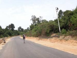 Vietnam | Süden, Phu Quoc bekommt Strom. Ein Mann hängt auf einem Masten einen Stromleitung verlegend, ein anderer steht mitten auf der Straße, hält das Kabel und beaufsichtigt den Arbeiter