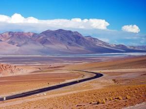 Chile   Das Altiplano beim Grenzübergang mit dem Bus über den Jama Pass von Salta in Argentinien nach San Pedro de Atacama. Die Straße führt mitten durch die gerade Fläche des Altiplano in bunten Farbtönen bei blauem Himmel
