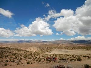 Chile   Extreme Weitsicht auf dem Altiplano beim Grenzübergang mit dem Bus über den Jama Pass von Salta nach San Pedro de Atacama. Weiße Schäfchenwolken werfen Schatten bei strahlend blauem Himmel über die bunte ebene Fläche