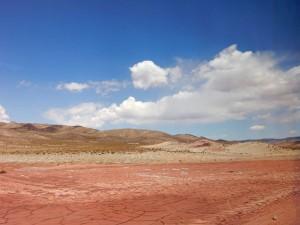 Chile   Das getrocknete Altiplano bei der Überquerung der Grenze mit dem Bus über den Jama Pass von Salta nach San Pedro de Atacama. Rote rissige Lehmerde im Vordergrund