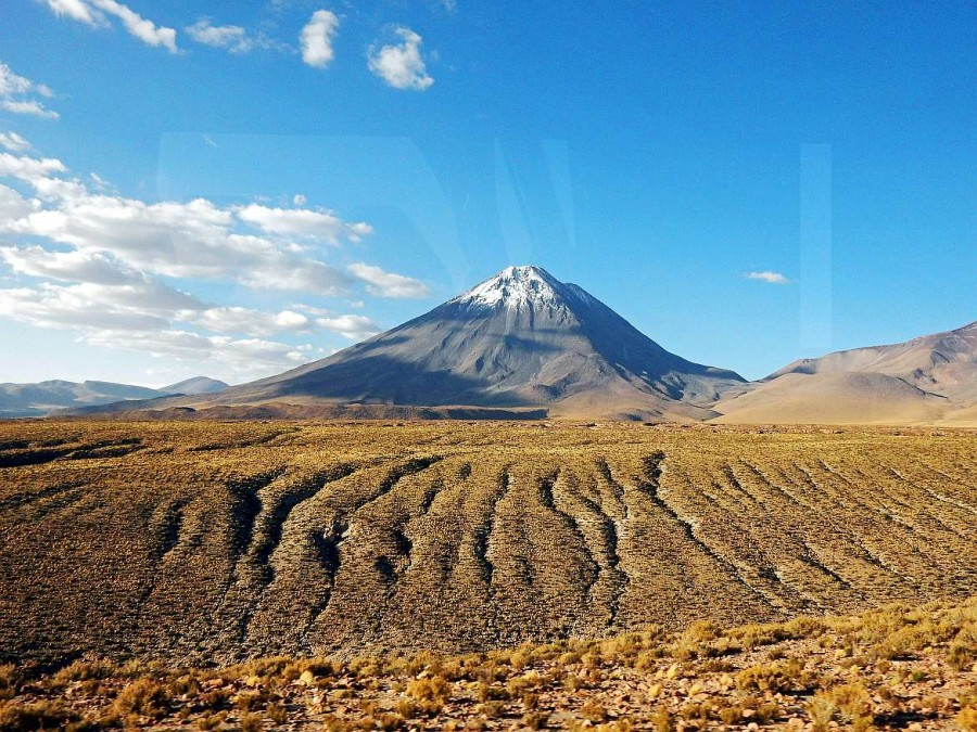 Chile   Der Vulkan Licancabur auf dem Weg mit dem Bus von Salta über den Jama Pass bis nach San Pedro de Atacama. Panorama auf die schneebedeckte Spitze des höchsten Vulkan um San Pedro de Atacama fotografiert aus dem Bus