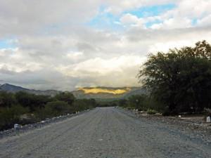 Region Salta, Argentinien | Straße zu den Ruinas del Quilmes bei Cafayate. Eine Schotterpiste führt zur alten Stadt mit Blick auf im Nebel liegende Berge