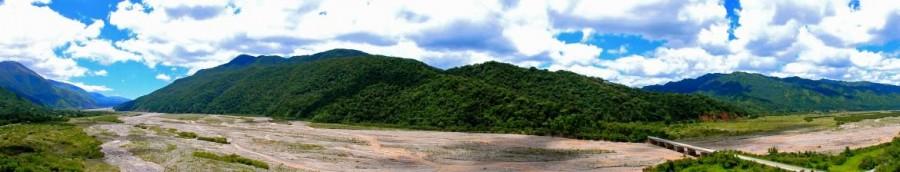 Argentinien | Panorama in der Nähe von San Salvador de Jujuy von Salta kommend. Ein Flusstal umzingelt von sattgrün bewachsenen Bergen