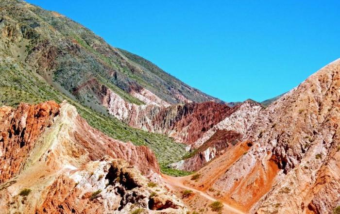 Argentinien | Panorama auf der Wanderung um den Cerro de los Siete Colores in Purmamarca. Ein kleiner Wanderweg führt durch bunte Berge bei blauem Himmel