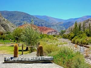 Argentinien | Willkommen in Purmamarca. Das Ortsschild von Purmamarca aus Holz vor bunter Bergkulisse mit einem kleinen Fluss und grünen Bäumen bei blauem Himmel