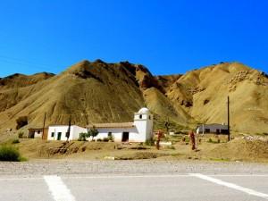 Argentinien | Kirche auf der Quebrada de Humahuaca. Eine weiße schlicht gebaute Kirche vor ockerfarbenen Berge bei blauem Himmel