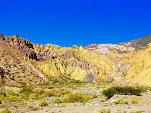 Region Salta, Argentinien | Ein Wechselspiel der Farben auf der Quebrada de Humahuaca. Gelb und rosafarbene bergkette vor blauem Himmel