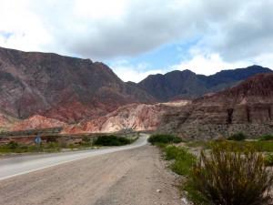 Argentinien | Abendstimmung auf der Quebrada de los Conchas von Cafayate nach Salta. Die untergehende Sonne vor bunter Bergkette mit einer Straße die sich hindurch schlängelt