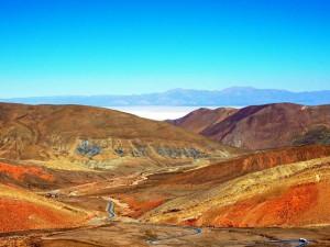 Argentinien | Panorama vom Altos de Morado Pass mit den Salinas Grandes im Hintergrund. Bunten Bergketten im Vordergrund bei blauem Himmel