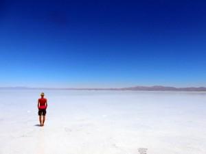 Argentinien | Karin im pinken Oberteil als Kontrast in der Salinas Grandes del Noroeste bei blauem Himmel