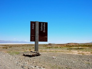 Argentinien | Ein Hinweisschild der Salzwüste Salinas Grandes del Noroeste vor blauem Himmel mit der Salzwüste im Hintergrund