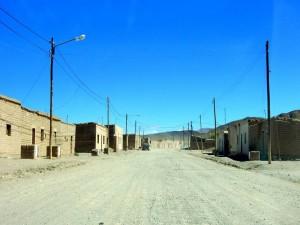 Argentinien | Antonio de los Cobres. Blick auf die staubige Straße mit ein paar verlassen aussehenden Häusern bei blauem Himmel