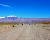 Argentinien-Tipps | Straßen sind gerne auch mal spontan gesperrt, wie hier auf der RN40 von San Antonio de los Cobres über den Pass Abra del Acay. Zwei Tonnen und ein quer darüber gelgtes Brett versperren die Pistenstraße, im Hintergrund schneebedeckte Berge bei blauem Himmel