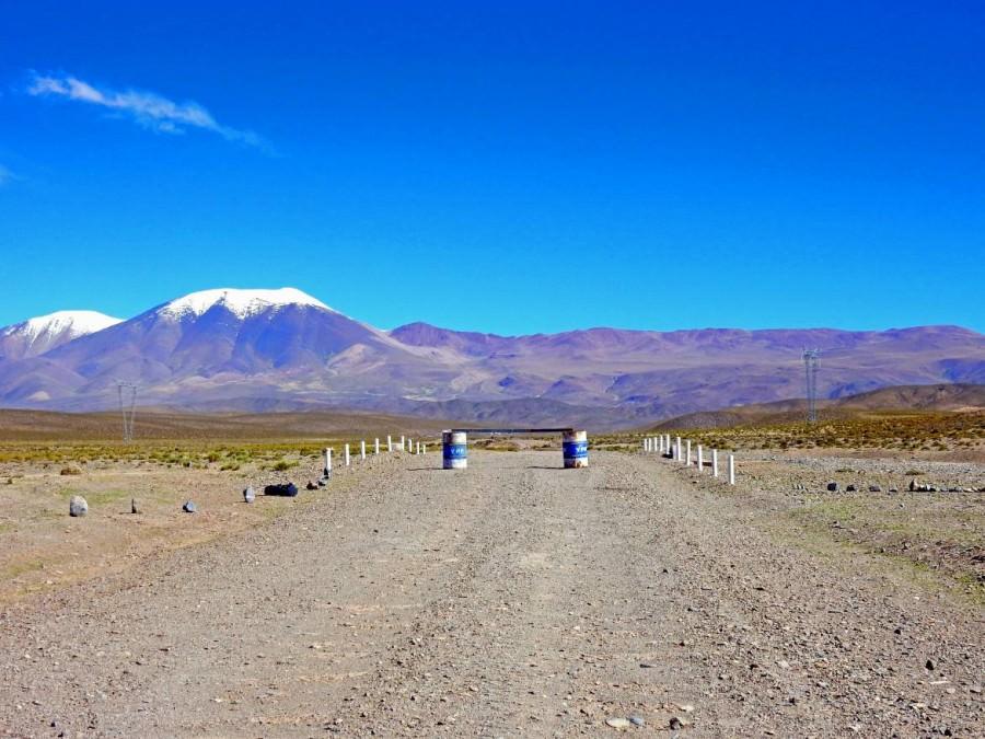 Argentinien | Straßensperrung auf der RN40 von San Antonio de los Cobres über den Pass Abra del Acay. Zwei Tonnen und ein quer darüber gelgtes Brett versperren die Pistenstraße, im Hintergrund schneebedeckte Berge bei blauem Himmel
