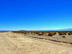 Argentinien | Straße nach San Antonio de los Cobres. Eine Schotterstraße führt durch eine flache verlassene Ebene mit ein paar Gräsern bewachsen und Bergketten im Hintergrund bei blauem Himmel