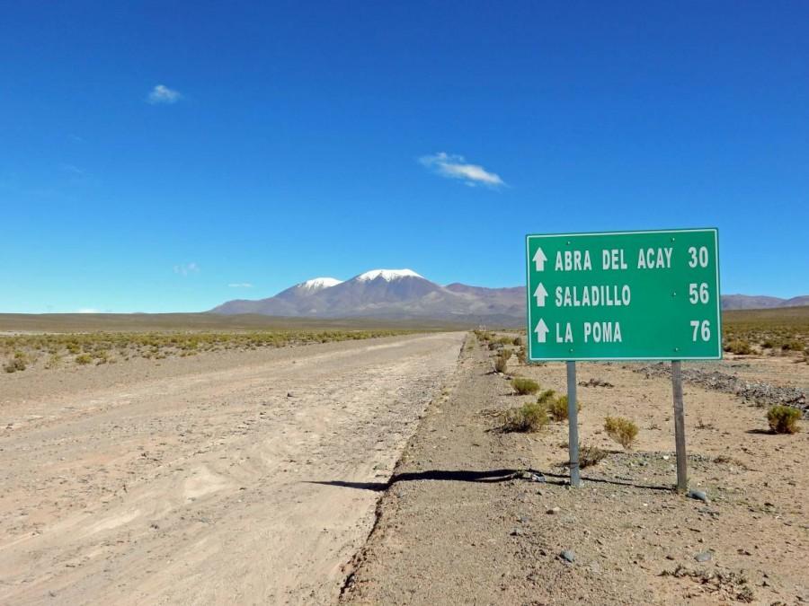 Argentinien | Wegweiser zum Abra del Acay und La Poma auf der Straße nach San Antonio de los Cobres. Schneebedeckte Berggipfel mit blauem Himmel im Hintergrund