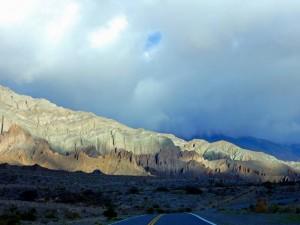 Argentinien | Mystische Stimmung beim Sonnenuntergang auf der RN 51 von San Antonio de los Cobres nach Salta. Dunkle Wolken, von der Sonne beleuchtete bunte Bergketten
