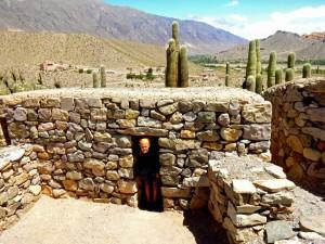 Argentinien | Klein sind die Inkahäuser in Pucara de Tilcara. Karin steht in der Tür eines aus Stein gebauten Hauses mit Dach aus Lehem