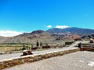 Argentinien | Die Ruinen der Inkastadt Pucara de Tilcara. Panorama auf die Stadt mit den bunten Bergen im Hintergrund, Henning auf einer Mauer sitzend