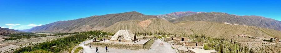 Argentinien | Panorama auf die Inkastadt Pucara de Tilcara mit Bergketten im Hintergrund, meterhohen Kakteen und kleinen flachen Häusern im Vordergrund