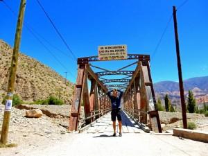 Argentinien | Der Weg in Tilcara führt über die Brücke zur alten Festung Pucara de Tilcara. Henning freut sich mit den Händen in der Höhe bei strahlend blauem Himmel