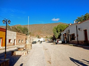 Argentinien | Hauptstraße in Tilcara. Eine staubige Pisten führt durch eine Straße mit flachgebauten Lehmhäusern in das Zentrum