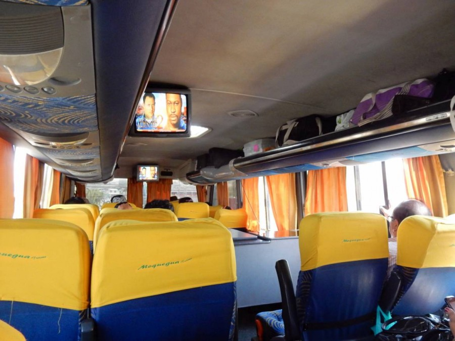 Peru | Chile, der Bus von Tacna nach Arequipa von Innen. Zwei Reihen von blauen Zweier-Sitze mit gelben Stuhllehnen, ein Fernseher an der Decke