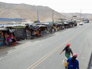Peru | Chile, Verkäuferinnen auf dem Weg mit dem Bus von Tacna nach Arequipa. Verkaufsbuden am Straßenrand gegenüber, aus dem Bus fotografiert