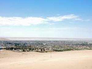 Chile | Peru, Ankunft in Tacna beim Weg über die Grenze Grenze von Arica nach Tacna. Die Stadt im Hintergrund, Wüste im Vordergrund bei blauem Himmel