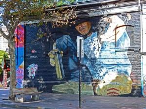 Chile | Graffiti im Stadtteil Bellavista in Santiago. Typ mit Spraydose in Großformat an einer schwarzen Hauswand