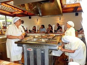 Chile | Zubereitung der Burger im Restaurant Fuenta Alemana in Santiago. Frauen mit Kopfbedeckung und weißen Kitteln stehen am Herd in der Mittel des Ladens und präperieren verschiedene Burger, hungrige Gäste sitzen um den Tresen