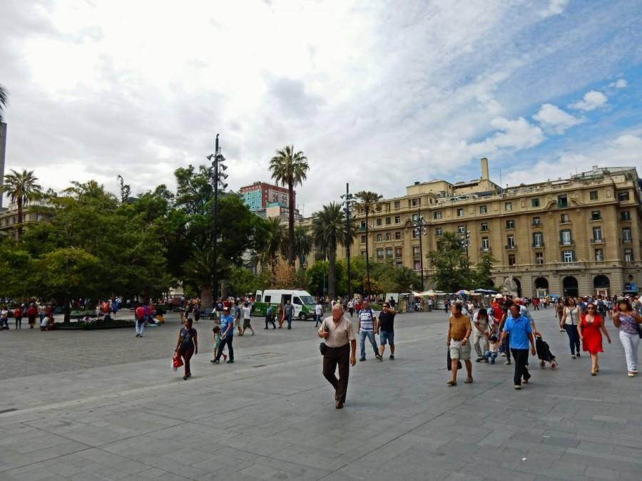 Santiago de Chile | Sehenswürdigkeiten: Plaza de Armas. Touristen und Einheimischen kreuzen den Platz, der mit Palmen bewachsen ist und von kolonialen großen Gebäuden umgeben