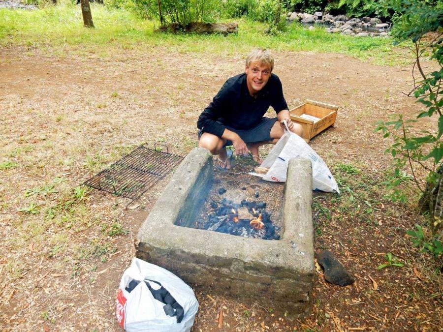 Chile | Temuco, Grillplatz im Conguillio National Park. Henning kniet vor dem Grill und macht Feuer