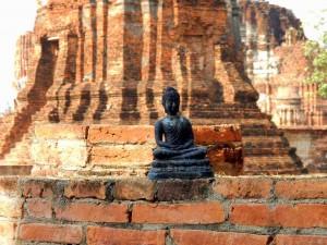 Thailand | Buddha in Ayutthaya. Ein kleiner schwarzer Buddha steht vor der rötlichen Fassade einer alten Tempelruine