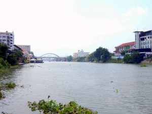 Thailand | Chao Phraya Fluss in Ayutthaya. Blick vom Boot auf den Fluss mit Wohnhäusern am Ufer