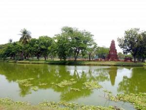 Thailand | Rama Public Park. Blick über einen See auf die grüne Wiese des Parks mit einigen alten Ruinen