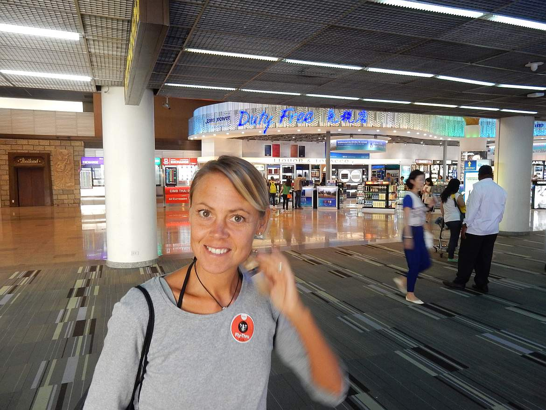 Thailand | Duty free Zone am Flughafen Don Mueang in Bangkok. Karin steht im Vordergrund zahlreicher bunter Verkaufsshops