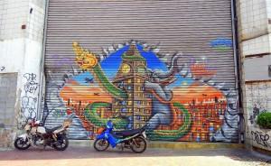 Thailand | Willkommen in Bangkok. Ein buntes Graffiti auf einem grauen Rolltor, zwei Mopeds im Vordergrund