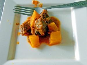 Thailand | Masamam Curry in der Kochschule in Bangkok. Rind, Kartoffeln und Currysoße auf einem Teller mit einer Gabel in Nahaufnahme