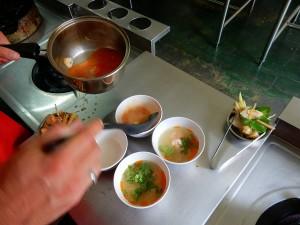 Thailand | Tom Yum Gung Suppe in der Kochschule in Bangkok . Henning verteilt die Suppe auf vier Schälchen
