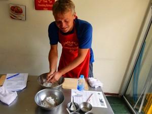 Thailand | Zubereitung von Kokosmilch in der Kochschule in Bangkok. Henning drückt das Wasser eine Kokosnuss aus