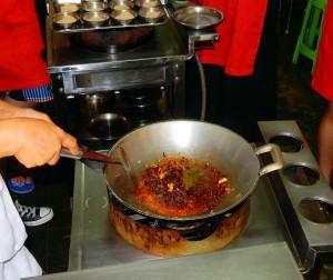 Thailand | Zubereitung von roter Currypaste in der Kochschule in Bangkok. Rotes Chilis werden im Wok gekocht und umgeschaufelt