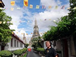Thailand | Wat Arun in Bangkok. Henning im Vordergrund des Tempels mit ein paar Fahnen als Wegweiser und 2 Mönchen die in orangefarbenen Kutten vor uns laufen