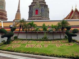 Thailand | Willkommen im Wat Po in Bangkok. Ins Gras geschriebener Willkomens-Gruß, der Tempel im Hintergrund